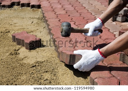 a worker laying red concrete paving blocks. - stock photo