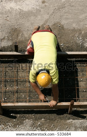 A worker lays steel mesh between formwork before cementing