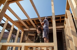 A worker measures a wooden workpiece with a meter. Building a house.