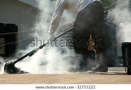 a worker mops out molten tar on a roof replacement job