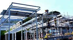 A worker on the top is laying corrugated steel plates to build steel deck for the floor structure or roof system while the other worker is erecting the scaffold tube to reach to a higher height.