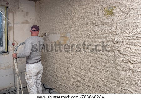 A worker plastered the interior walls with a plaster pump machine on the construction of a private house. Concept; construction site