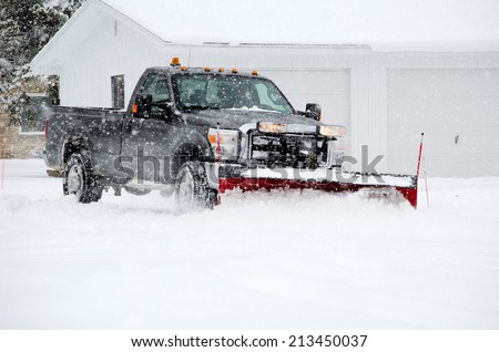 a worker plows heavy white snow during a Michigan winter