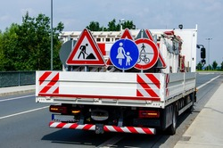 A worker's truck with roadsigns at a road construction site