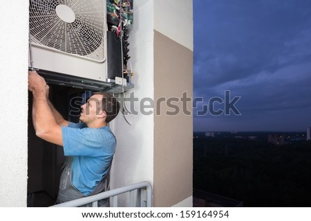 A worker sets split system air conditioner in the evening