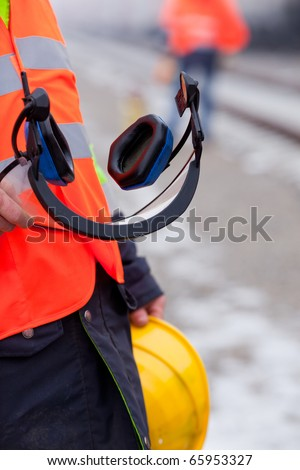 a worker shows his helmet and ear protectors