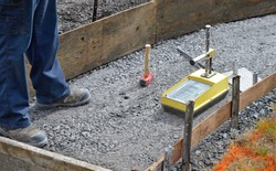 A worker tests the compaction of crushed stone - or gravel - before installing a new sidewalk