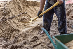 A worker use the shovel to fill the sand into the wheelborrow for construction of new house. Construction tools.