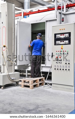 A worker working on the electrical panel in the factory, factory life