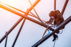 A working man is an engineer and welder in a construction overall, a welding mask is cooking metal and is sitting on a metal structure at an altitude against the blue sky