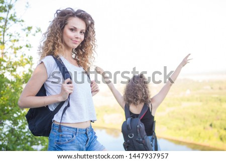 A world without borders. Stunning journey of two girls in the mountains. Two girls at the top of the mountain rejoice in a successful ascent. Concept of success and travel #1447937957