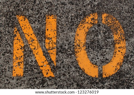 A worn and yellow \'No\' sign stenciled on a  pavement