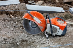 A worn, bright orange petrol saw with a diamond cut-off wheel set against a blurred background of rubble, concrete parapets and taut blue thread.