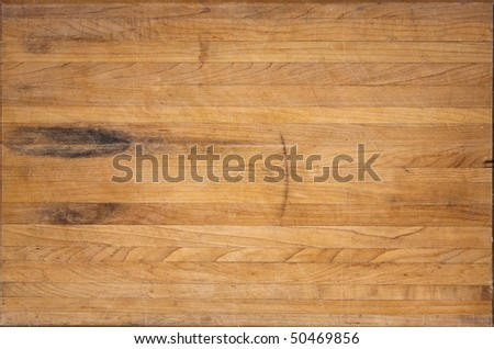 A worn butcher block cutting board sits as a background