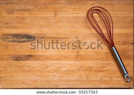 A worn butcher block cutting board sits as a background with a wire whisk located to one side.