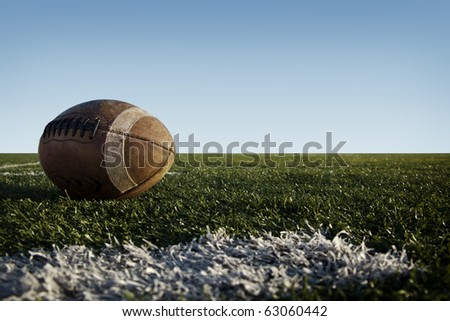A worn football laying on a grass field with a blue sky.