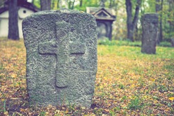 A worn sandstone grave marker in the shade on a very bright day. There is no text visible on the stone, but there is some moss on the top. Tombstone and graves in an ancient church graveyard. toned