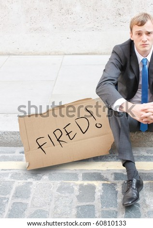 A worried business man sitting on the street