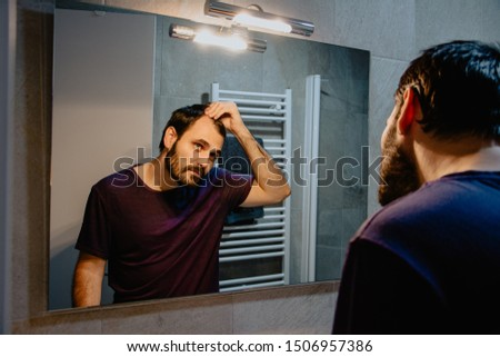 A worried young white man looks at himself in the mirror and inspects his premature receding hairline. Attractive Caucasian male adult in his 30s concerned about losing hair. Male pattern baldness