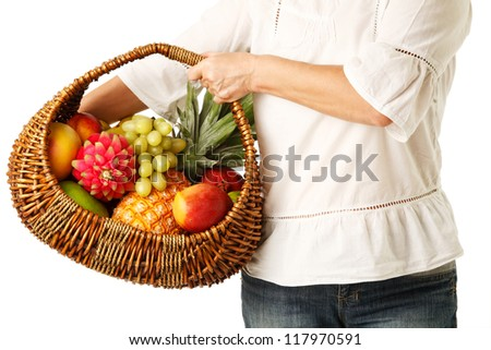 A Woven basket full of different fruit in hands of women.