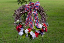 A wreath of blue, white and red flowers with Confederate flag themed ribbons. This wreath was placed in Point Lookout Prisoner of war camp where 3384 Confederate captives died due to bad conditions