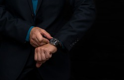 A wristwatch on the hand of a business man in a dark blue jacket.