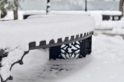 A wrought-iron carved black bench on a city street is littered with an even layer of snow. Zigzag border of snow and wooden seat. An old city park. Restrained range of colors in black and white.