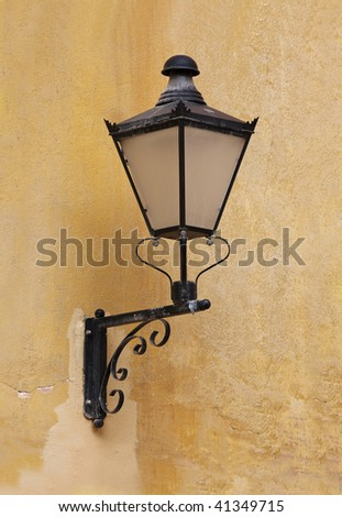 A wrought iron lamp on a weathered wall in Italy