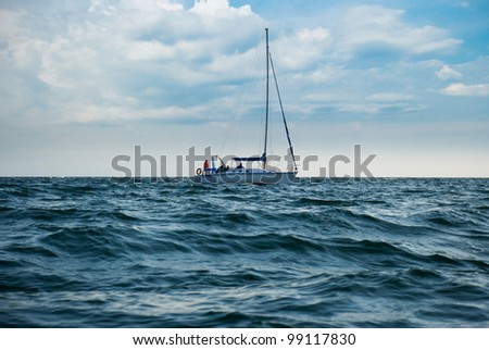 A yacht in a stormy sea. A boat lowered the sails and unrecognisable people