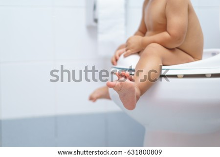 A year and 3 months old Asian baby sit on a kid bathroom accessory toilet