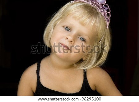 A 4 year old  blond little girl with a pink tiara. Isolated on black