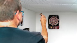 A 50 year old blond man plays darts. An electric dart machine shows his hits in a duel. The dartboard is hanging in a party cellar.