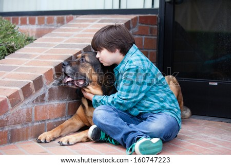 A 10 year old boy and his dog lying down on the sidewalkA 10 yeqr old boy and his dog sitting down on the sidewalk