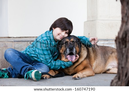 A 10 year old boy and his dog sitting down on the sidewalk
