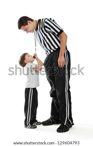 A 4 year old boy blowing teen referee's whistle isolated on a white background