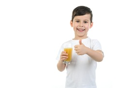 A 6-year-old boy in a white T-shirt holds a glass with citrus juice on a white background. Isolated background. Baby loves orange juice. Positive emotions. healthy food for children, schoolchildren