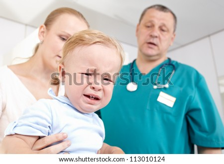 A 1,5 year-old boy is frightened and crying in a medical study. The doctor and the baby'Â?Â?s mother are at a loss. Shallow dof. Focus is on the boy.