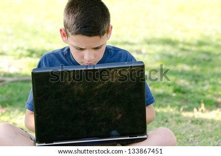 A 10 year old boy looking at his computer screen while sitting in the park.