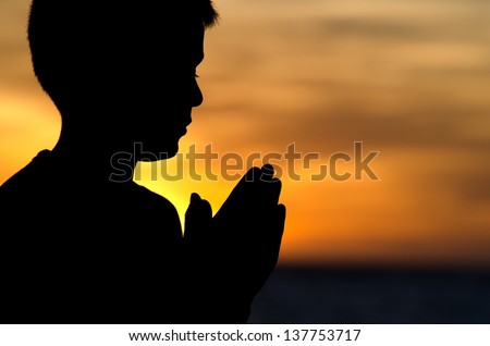"A 10 year old boy praying at sunset at ""Big Beach"" in Maui."