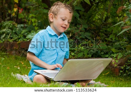 a 5 year old boy sitting on the grass in his backyard using a laptop