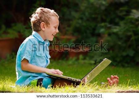 a 5 year old boy sitting on the grass in his backyard using a laptop on a bright sunny day
