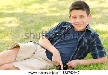 A 10 year old boy smiling while he touches his tablet with his finger.