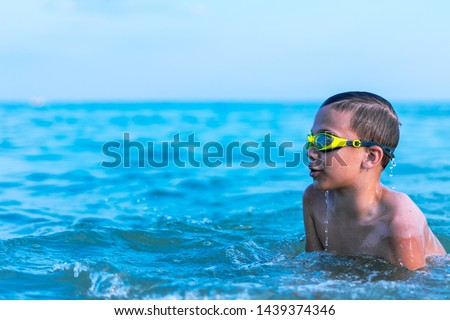 A 10-year-old boy swims in the sea at dawn with glasses for swimming #1439374346
