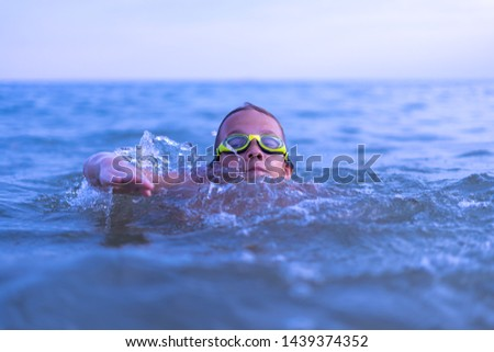 A 10-year-old boy swims in the sea at dawn with glasses for swimming #1439374352