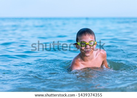 A 10-year-old boy swims in the sea at dawn with glasses for swimming #1439374355