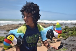 A 4 year old brazilian child with curly hair shooted at a paradise rocky beach in the northeast region of Brazil.  He wears water wings. His t-shirt has the following in french: