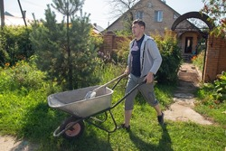 A 30-year-old caucasian man carries a garden wheelbarrow for loading sand to fill the paths with concrete at his summer cottage
