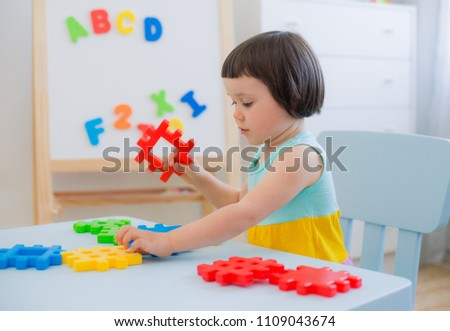 A 3 year old child plays at a table with colorful toy blocks. Children play with educational toys in the kindergarten or room. Preschoolers gather at the table the puzzle out of plastic blocks. #1109043674