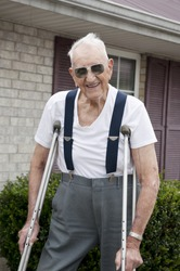 A 93 year old elderly man with crutches, standing alone outside his apartment with a big smile on his face