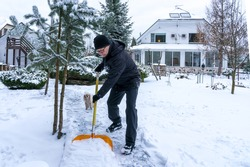 A 61-year-old European with his poodle shovels snow from a walkway outside his home. Winter old age lifestyle concept